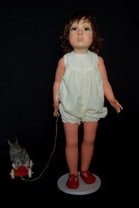 Wendy Mayer | Duck Rabbit (Rabbit) | 2012 | Doll, wax, acrylic eyes, hair, taxidermied rabbit, wooden pull along toy | 78x48x21cm