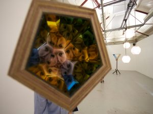 Steven Morgana | Gyrating Cooperative Kaleidoscope (Stand Off) | 2011 | Blue and yellow mirrors, plywood, rotating motor, steel tether & carabiner | 16x16x50cm